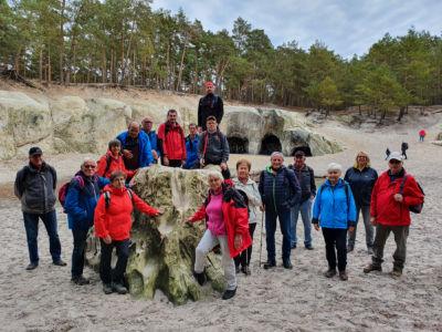 Sand unter den Füßen - Die Wandergruppe vor den großen Sandsteinhöhlen
